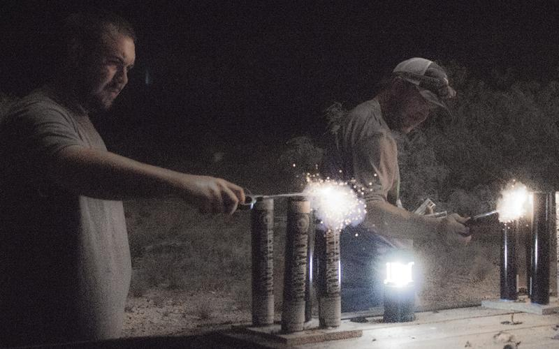 From left, Dokken Phillip and Shae Arquitte light fireworks during the Salute on the Salt Flats July 4 outside Canyon Road Barn and Grill. Show organizers aim to return bigger and better in 2018.