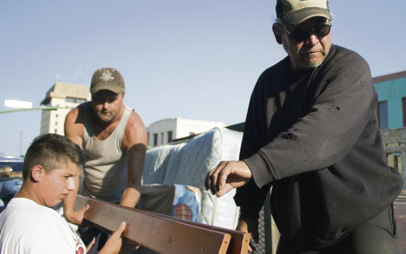 Isaac Reyes, Tom Alfred and Joe Hernandez load bed frames and mattresses up for delivery Thursday.
