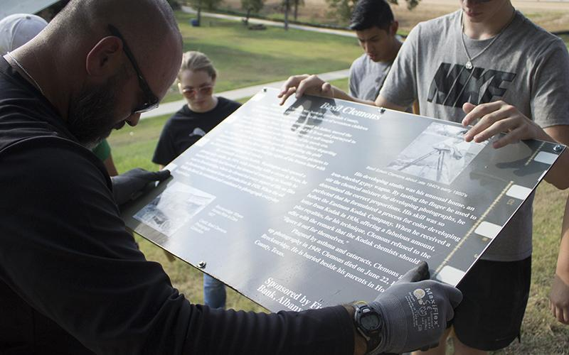 BHS Assistant Football Coach Brian Valenzuela and  senior student Braxton Post steady a historical way marker inside Breckenridge Park.