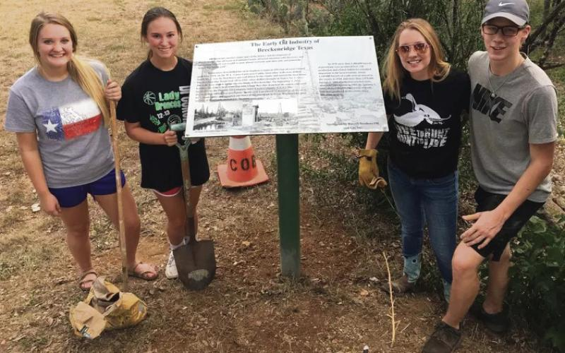 From left, Breckenridge High School students Diana Patterson, Mackenzie Harris, Elyssa Glick and Braxton Post pose for a photo after placing historical markers and planting tress along the walking trail of Miller Park in Breckenrige as part of a project through TMCN.