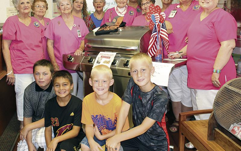 Area children and the Stephens Memorial Hospital Auxiliary pose for a photo during an event in June.