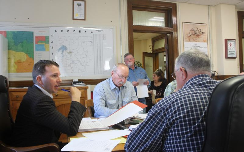 County Judge Michael Roach discusses budgeting with other county commissioners. BA photo by James Norman