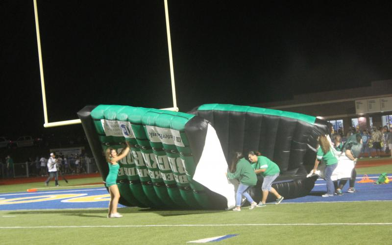 Buckaroo helpers try flip the entrance tunnel and stop it from blowing away before the second half on Friday night. Weather did not do anybody any favors, as the second half had rain throughout. BA photo by James Norman