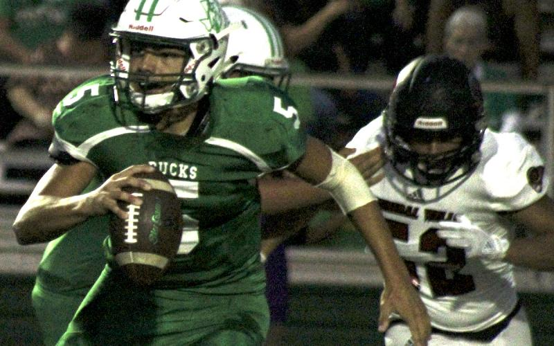 Breckenridge junior quarterback Kevin Franco scrambles away from an oncoming defender.