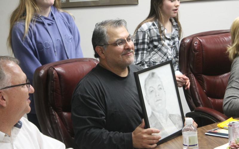 Board Member Pat Escalon holds his portrait up. BA photo by James Norman