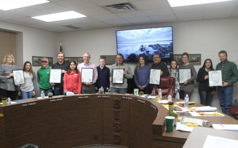 The board poses with students who drew their portraits in honor of School Board Appreciation Month. BA photo by James Norman