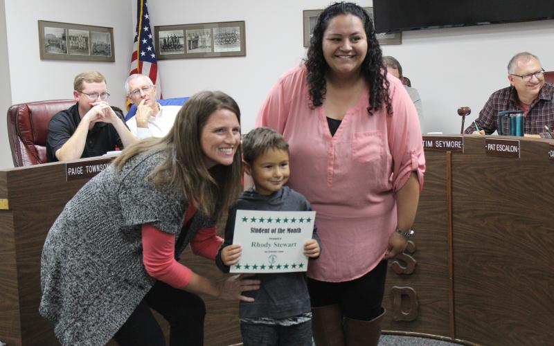 The principal at East Elementary is posing with Kindergarten student Rhody Stewart and his classroom teacher Teresa Guardiola at the BISD board meeting, where he was recognized as the Student of the Month for October. He represented for East Elementary.