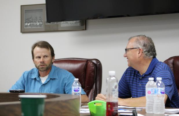 Tim Seymore (right) talks to Board President Graham Reaugh at the BISD school board's May meeting. BA photo by James Norman