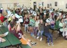 "Students at South Elementary hold up their recently donated book ""Wonder"" as part of a multi-class project."
